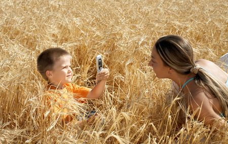 lovely kid picturing mom with cell phone photo