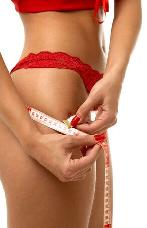 fit girl in red underwear measuring hips photo