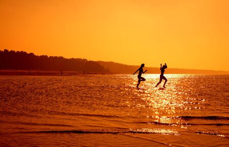 silhouette image of two running girls in water Stock Photo - 521742