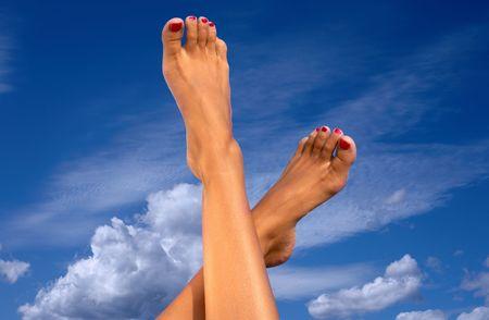 pieds sexy: Femme jambes sur ciel bleu avec des nuages  Banque d'images