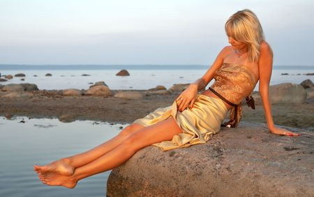 lovely girl relaxing on the rock photo
