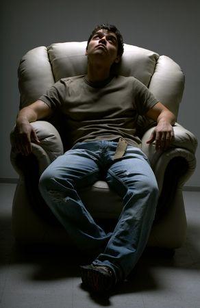 entspannter junger Mann in wei�em Stuhl