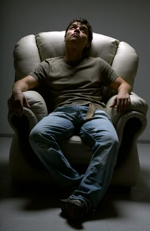 relaxed young man in white chair