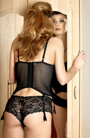 bodice: lovely lady in black lingerie looking into mirror