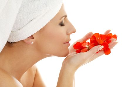 lovely woman smelling red flower petals photo