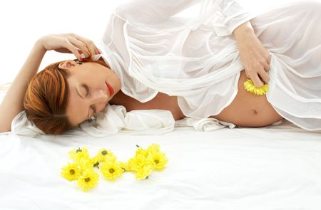 beautiful pregnant woman with yellow flowers in bed Stock Photo