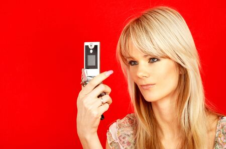 lovely blond with phone over red background photo