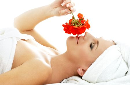lovely woman in spa smelling red flower photo