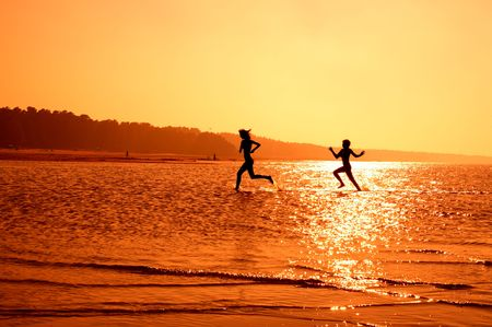 silhouette image of two running girls in water Stock Photo - 606227