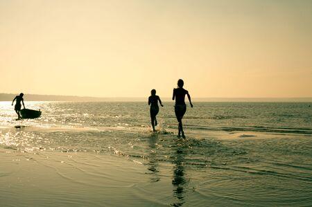 Silhouette Bild von zwei M�dchen laufen und muskul�s Mann im Wasser
