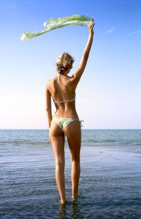 signalling: pretty blond in bikini with green scarf in water Stock Photo