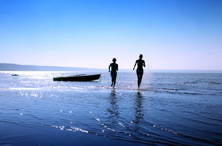 Imagen de la silueta de dos niñas corriendo en el agua  Foto de archivo - 610115