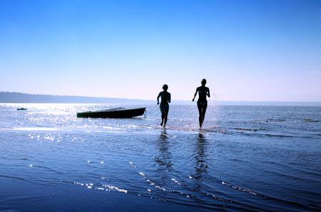 Imagen de la silueta de dos ni�as corriendo en el agua  Foto de archivo - 610115