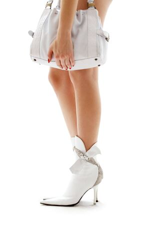 closeup of beautiful legs in white boots with white purse Stock Photo - 614326