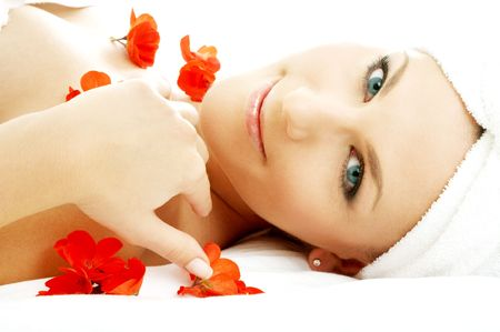 beautiful lady with red flower petals in spa photo