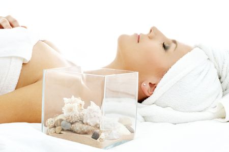 beautiful lady in spa salon with sea shells in glass cube photo