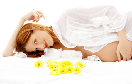 fruition: beautiful pregnant woman with yellow flowers in bed Stock Photo