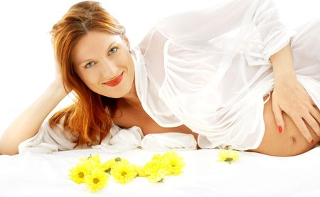 beautiful pregnant woman with yellow flowers in bed photo