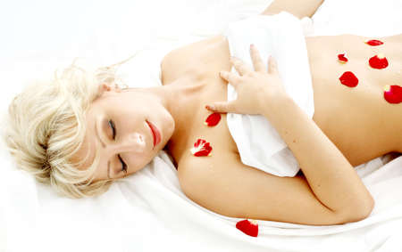remedial: lovely blond with rose petals relaxing in spa Stock Photo