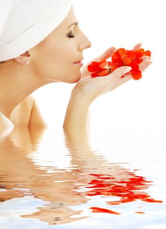 lovely woman smelling red flower petals in water