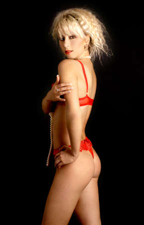 lovely blond with pearls in red lingerie over black background Stock Photo - 720098