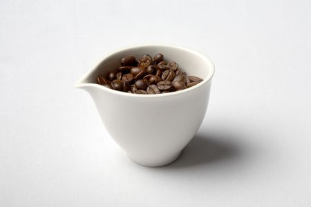 bar ware: white porcelain cup full of colombian coffee beans