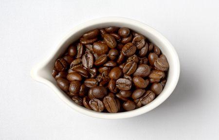 cafe colombiano: taza de porcelana blanca llena de granos de caf� colombiano