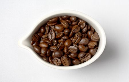 white porcelain cup full of colombian coffee beans photo