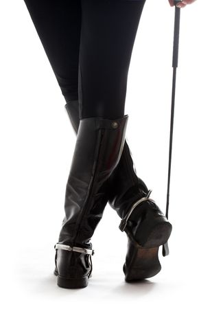 dominacion: Hermosas piernas jinete en cuero negro con botas de equitaci�n de los cultivos m�s blanco  Foto de archivo