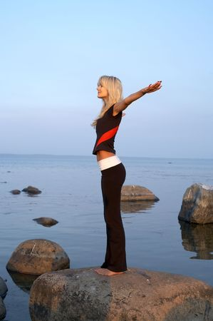 vivifying: picture of fit girl meditating at the seashore