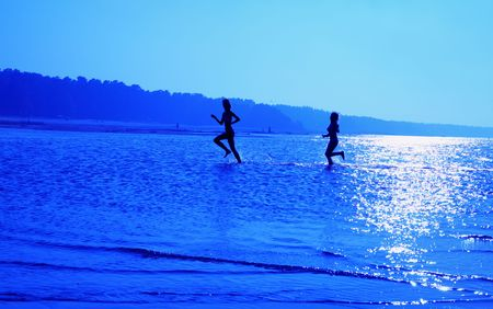 silhouette image of two running girls in water photo