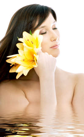 topless brunette: topless brunette with yellow lily flowers in water
