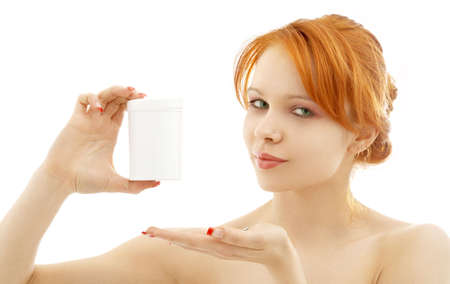 lovely redhead showing blank medication container over white photo