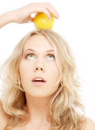 healthy blond holding lemon on her head over white Stock Photo - 837346