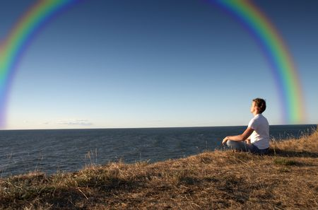 and harmony: meditation at the seashore with big rainbow