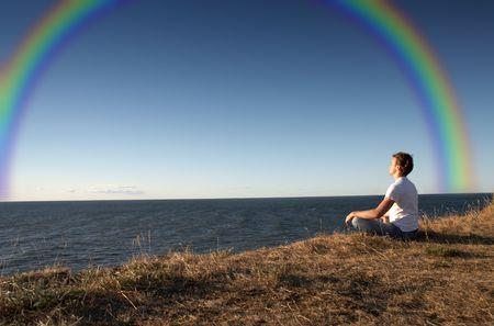 Meditation an der Küste mit großen Regenbogen