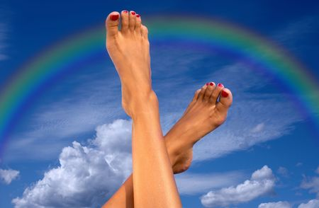 vivifying: female legs over blue sky with clouds and rainbow