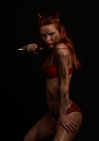 dark red devil girl with a knife over black Stock Photo - 859429