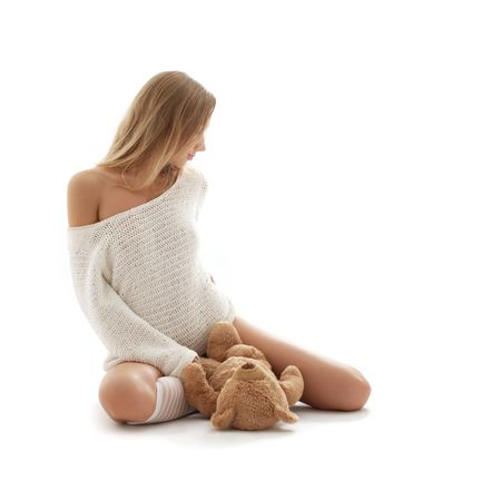 innocent: picture of lovely blond in white sweater with teddy bear Stock Photo