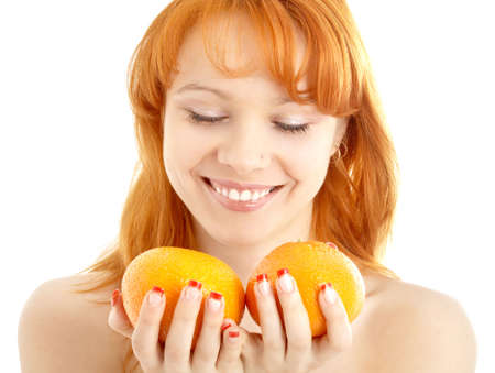 picture of cheerful redhead holding two oranges over white photo
