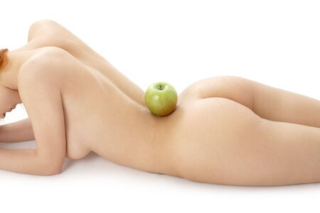 naked redhead with green apple on her spine over white Stock Photo - 877386