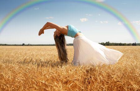 Bild der Frau, die sich auf der Wiese mit Regenbogen -  Lizenzfreie Bilder
