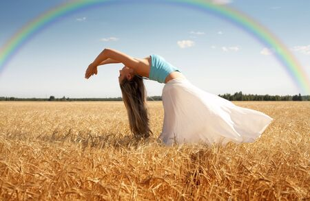 vivifying: picture of stretching woman in the meadow with rainbow