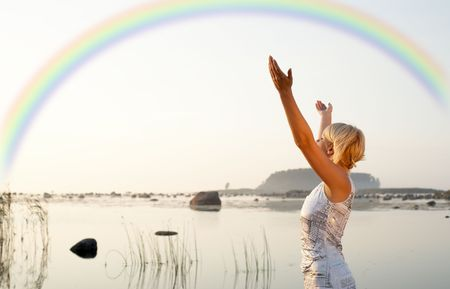 vivifying: picture of pretty blond raising hands to the rainbow