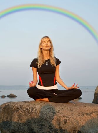 fiit girl meditating at the seashore under rainbow Stock Photo - 881203