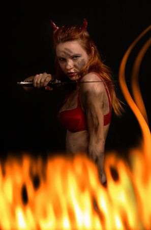 dark red devil girl with a knife in burning fire Stock Photo - 881206