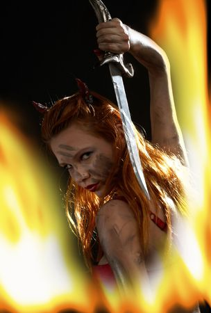dark red devil girl with a knife in burning fire Stock Photo - 883058