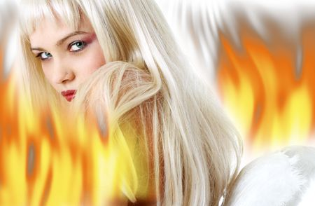 angel alone: lovely blond with angel wings surrounded by fire Stock Photo