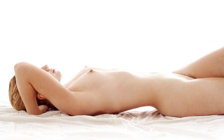 femme se deshabille: l'image classique d'une bonne femme nue dans un lit