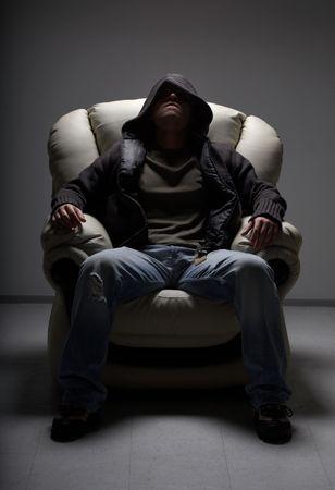 implacable: Sombre portrait de l'homme dangereux assis dans chaise blanche